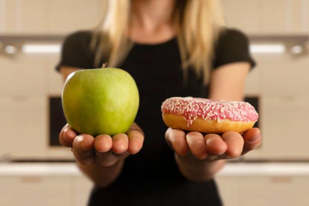 在甜甜圈和蘋果之間選擇 - 不健康飲食 個照片及圖片檔