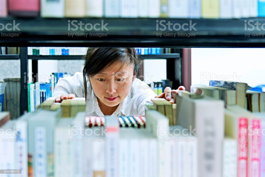 choosing book in library stock photo