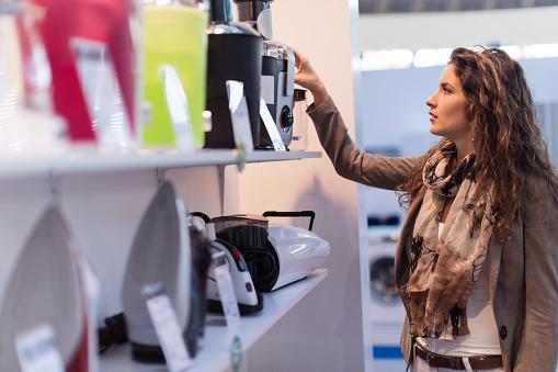 Beautiful woman choosing new electric juicer in homeware store