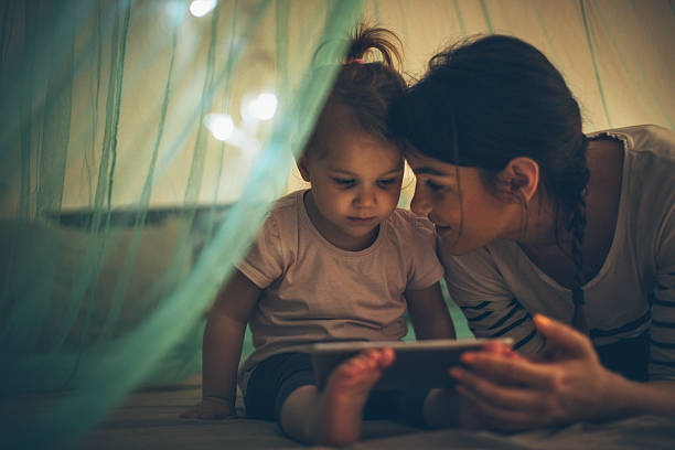 Choosing her favourite bedtime ebook Mother reading fairytale to her daughter on e-reader before bedtime bedtime stock pictures, royalty-free photos & images
