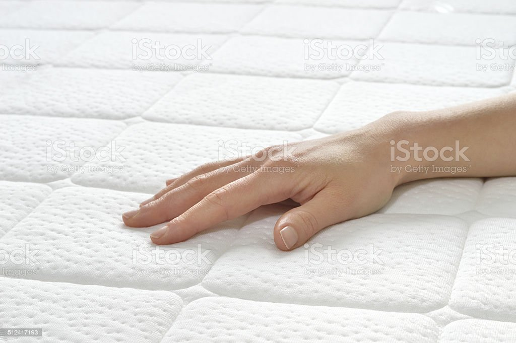 Choosing mattress and bed. Choosing mattress and bed. Close-up of female hand touching and testing mattress in a store. Copy space. Backgrounds Stock Photo