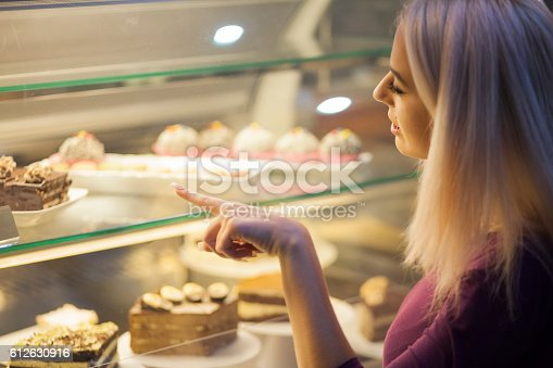 Young female looking for the right cake. Full of sweets in a sweets shop.
