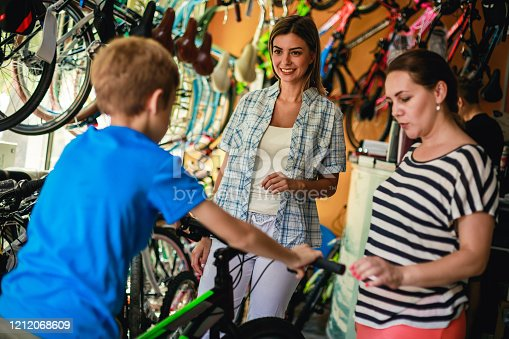 Selective focus of a happy saleswoman assisting  mother and son to purchasing his first bicycle in a specialised store.