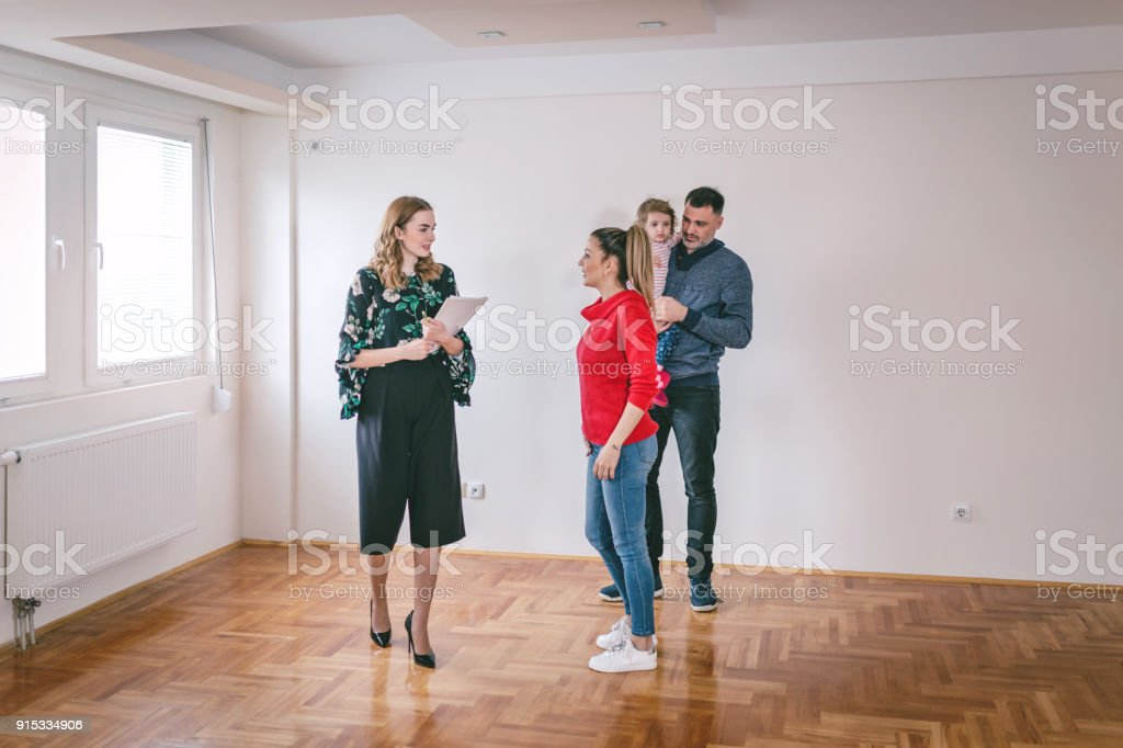 Choosing the new apartment Lovely married couple with child, looking to buy a new apartment with a help of a real estate agent. Adult Stock Photo