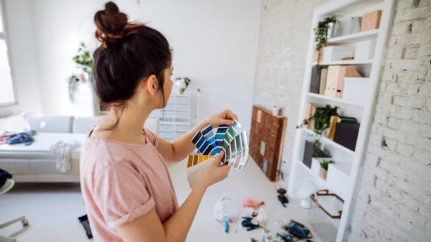 Choosing the right color for my wall Young woman during reconstruction of apartment, holding color chart and choosing the right color for the wall public housing stock pictures, royalty-free photos & images