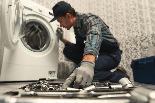 istock Choosing the right tool. Plumber repairing washing machine 1170038003