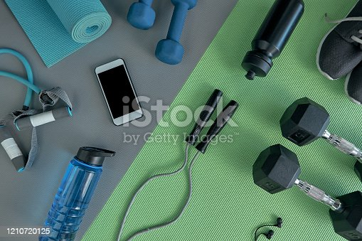 High angle shot of a variety of workout equipment laid out on a green exercise mat before a workout