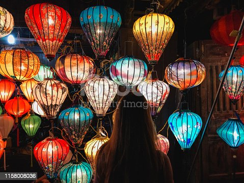 A rear-view shot of an unrecognisable woman standing in a market stall looking at the homemade lanterns on display.