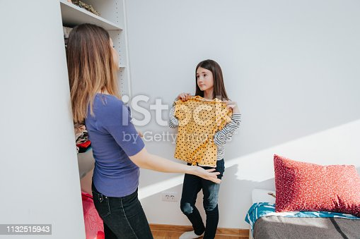 mother helping her preteen daughter to pick out clothes out of a full closet of things