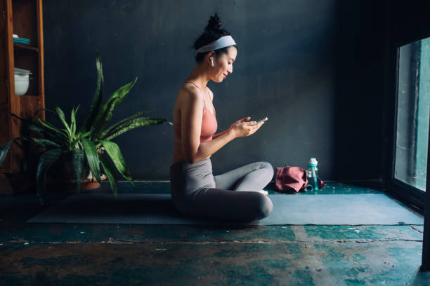 choosing workout music: asian woman with earphones sitting on the exercise mat and setting up a playlist on her smarphone - exercise at home stock pictures, royalty-free photos & images