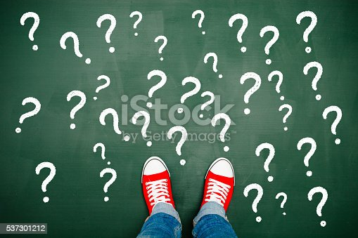 Someone wearing red sneakers in front of many question marks