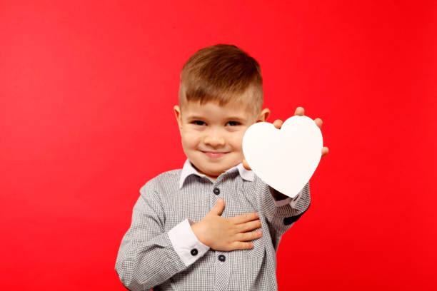 Chłopiec 4 lata trzyma białe serduszko z papieru Chłopiec 4 lata trzyma białe serduszko z papieru alternative pose stock pictures, royalty-free photos & images