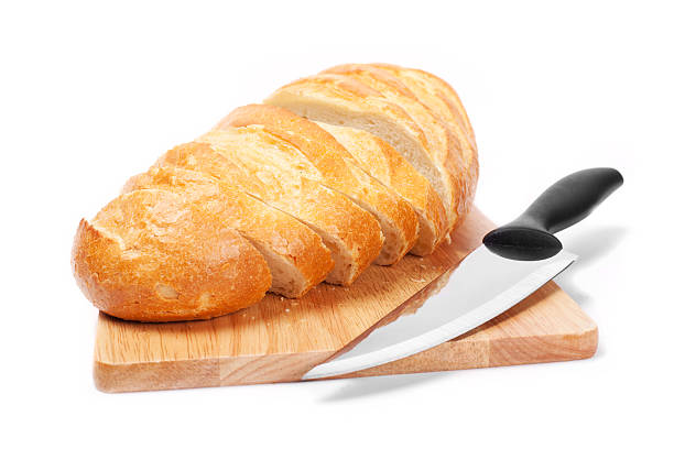 Chopped bread with knife on wooden utensil stock photo