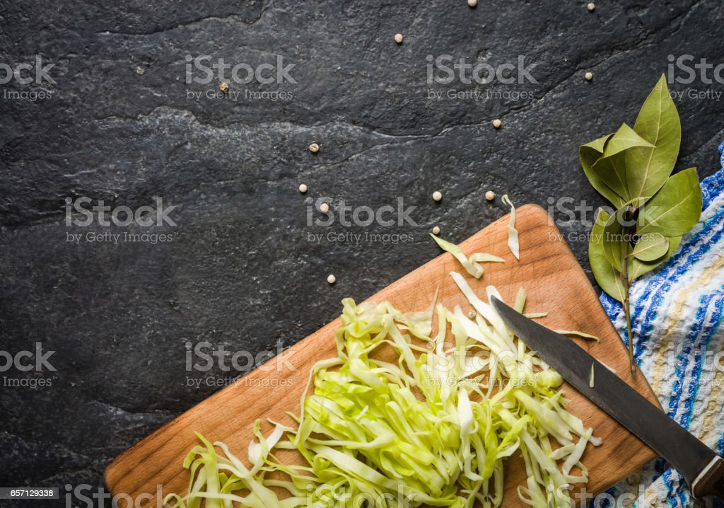 Chopped cabbage on a black stone background. stock photo
