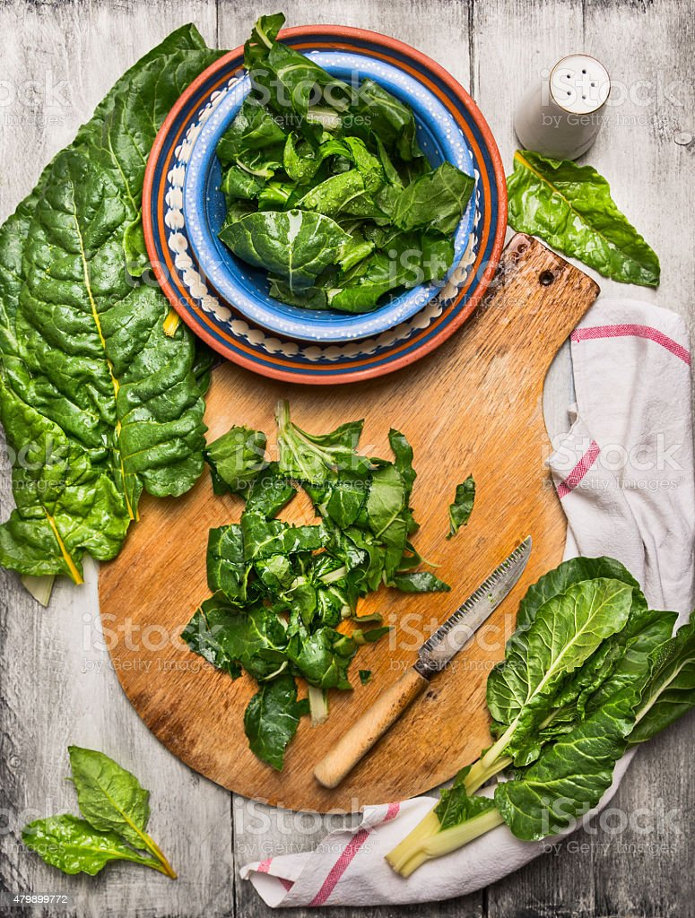 Chopped chard leaves on wooden cutting board with knife stock photo