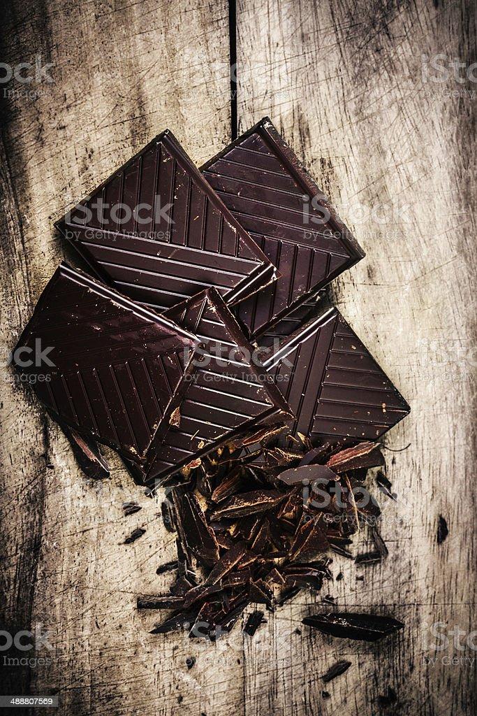 Chopped Chocolate Bar on wooden background closeup. Broken stock photo