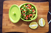 fresh vegetable salad with tomato, cucumber and green onion on Cutting board. Chopped cucumber tomato salad in a green bowl. Lemon cut in half