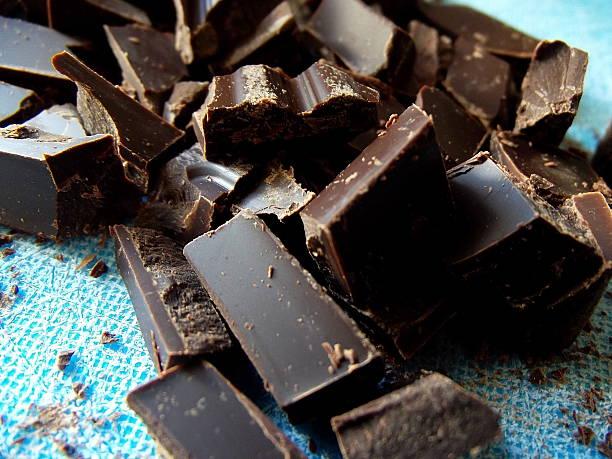 chopped dark chocolate on blue cutting board - pure chocola stockfoto's en -beelden