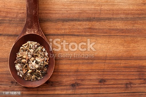 Top view of wooden spoon with chopped dried dandelion plants used for tea over table
