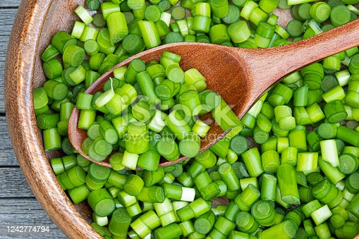 chopped green garlic stalks in wooden plate, cooking vegetarian dish, healthy food