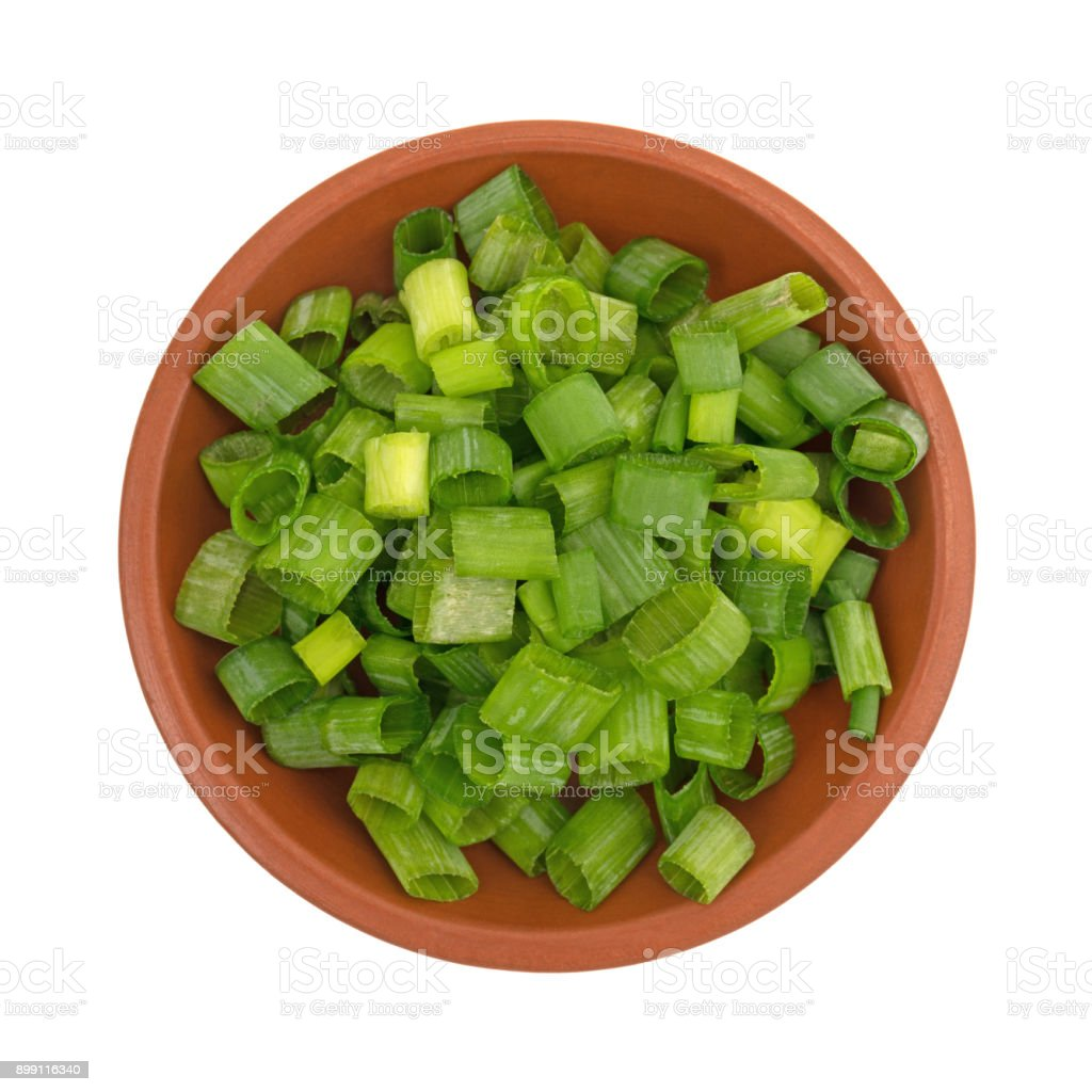 Chopped green onions in a small red clay bowl stock photo