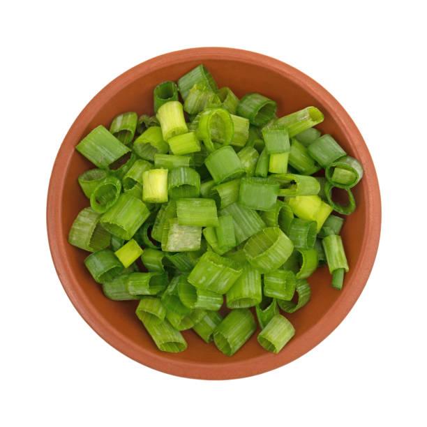 gehakte groene uien in een kleine rode klei kom - bosui stockfoto's en -beelden