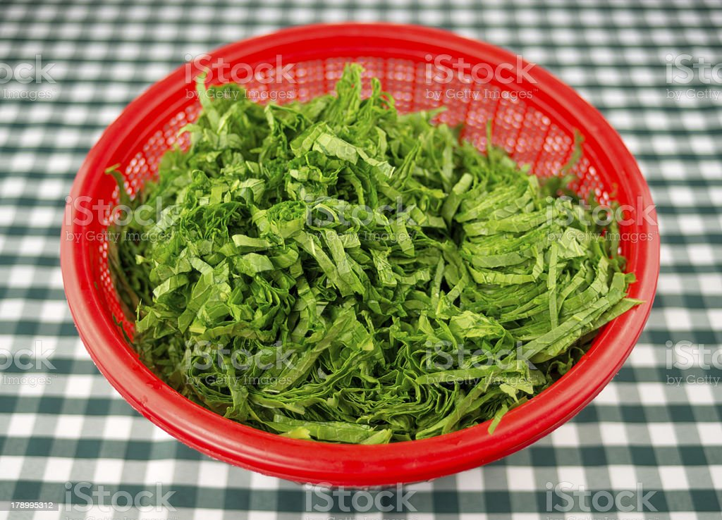 Chopped mustard greens in a red strainer bowl royalty-free stock photo
