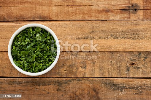 Top view of white bowl full of chopped parsley over wooden table
