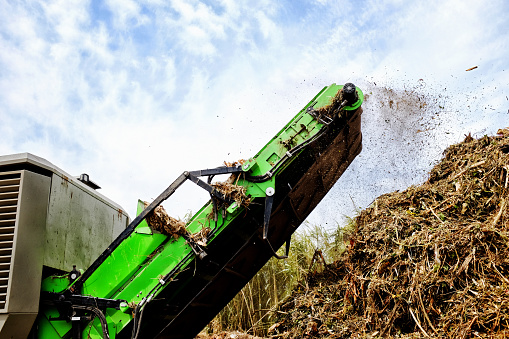 A huge green machine sprays out pulverized garden refuse onto a giant compost heap at a municipal recycling plant.