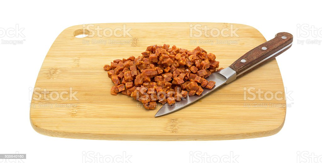 Chopped pepperoni pizza topping on cutting board with knife stock photo