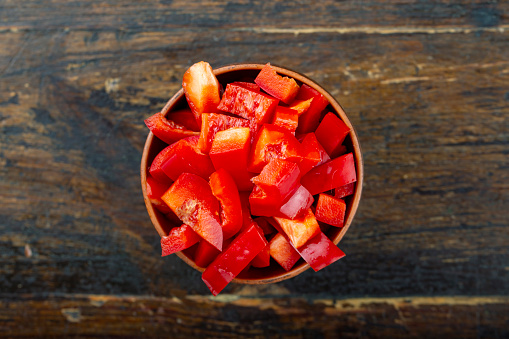 chopped red bell pepper in a plate on a brown wooden background.