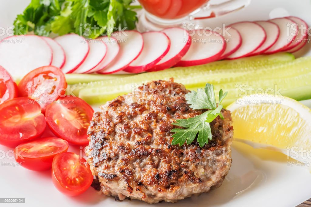 Chopped steak cutlet cooked on grill on white plate zbiór zdjęć royalty-free