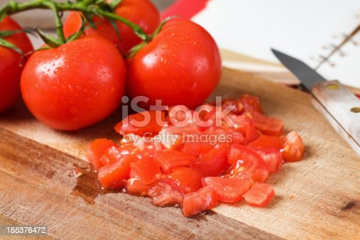 Chopped and whole vine ripened tomatoes on a wood cutting board with a kitchen knife and cook book.  Focus on the front chopped tomatoes.