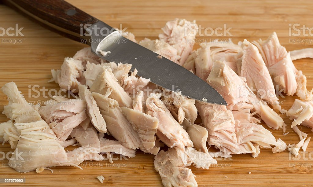 Chopped turkey on cutting board with knife stock photo