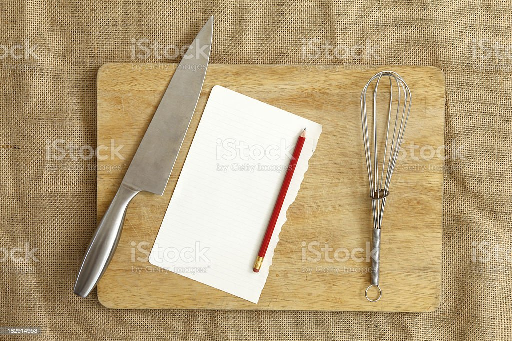 Chopping board and utensils with blank paper stock photo