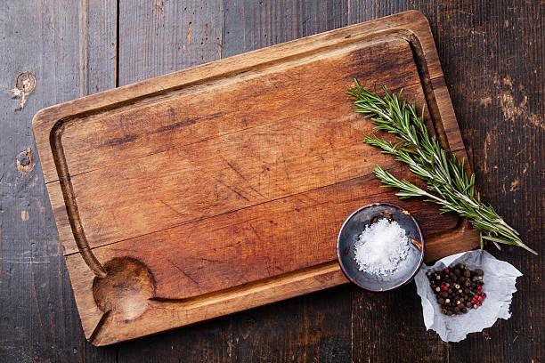 Chopping board, seasonings and rosemary stock photo