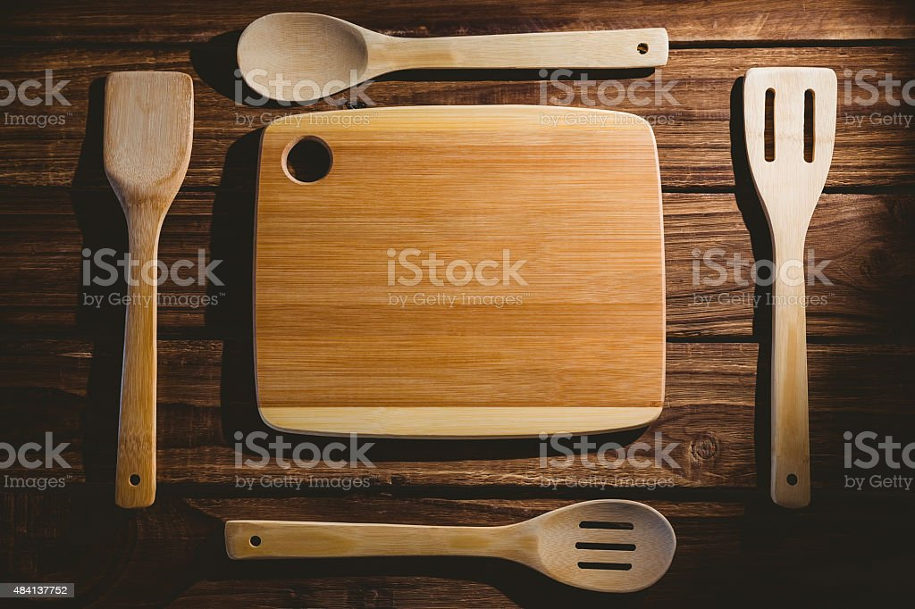 Chopping board with wooden utensils stock photo