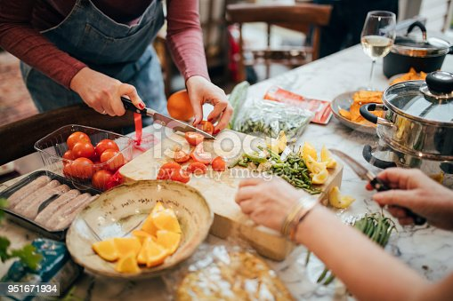 Two woman are chopping tomato's and vegetables