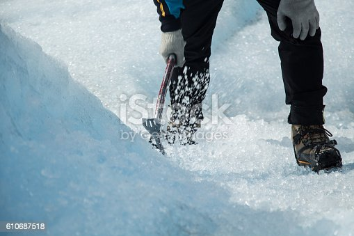 Man chopping ice with a pickaxe on the Perito Moreno Glacier