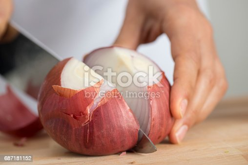 Woman chopping onion, close up.