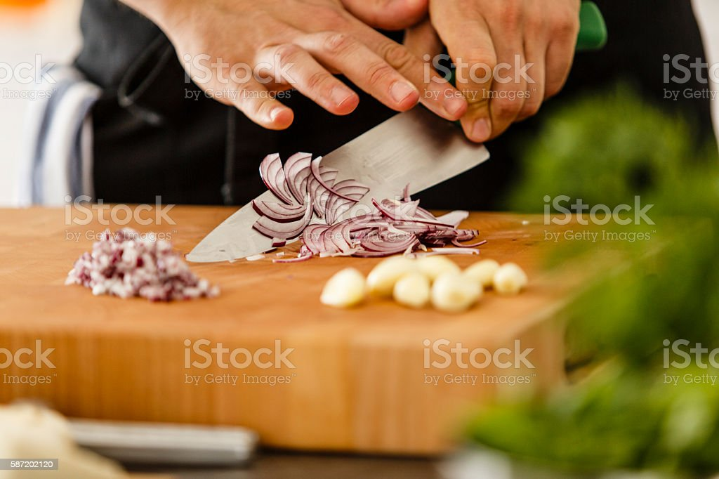 Chopping red onion on cutting board stock photo