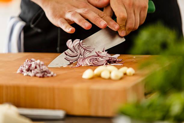 chopping red onion on cutting board - ciąć zdjęcia i obrazy z banku zdjęć