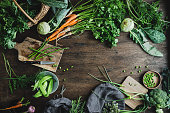 High angle view of fresh vegetables on a wooden chopping board. Cutting healthy vegetables for making salad over wooden table.