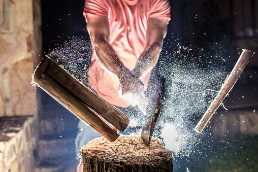 A man chops a piece of firewood. In the same moment as the wood splits the photograph is taken with a backlit flash. Freezing all the small particles that explodes.