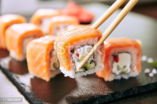 istock Chopstick holding Sushi Rolls Set with Salmon and Cream Cheese and Cuccumber on Black Slate Plate Close Up. Uramaki, Nori Maki or Futomaki Sushi with Trout Fillets, Soy Sauce and Wasabi 1176929581