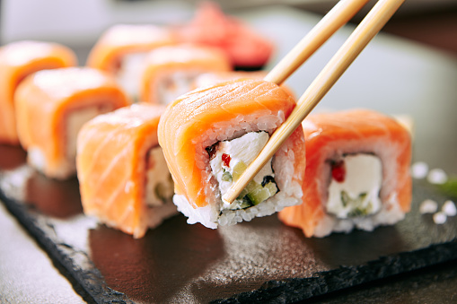 Chopstick holding Sushi Rolls Set with Salmon and Cream Cheese and Cuccumber on Black Slate Plate Close Up. Uramaki, Nori Maki or Futomaki Sushi with Trout Fillets, Soy Sauce and Wasabi