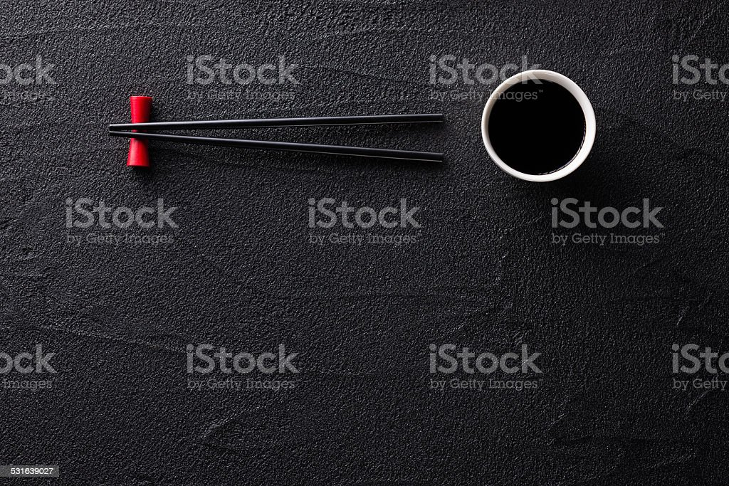 Chopsticks and bowl with soy sauce on black rock stock photo