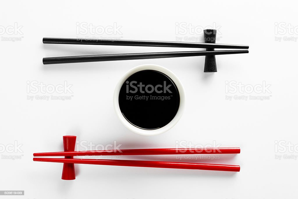 Chopsticks and bowl with soy sauce on white background stock photo