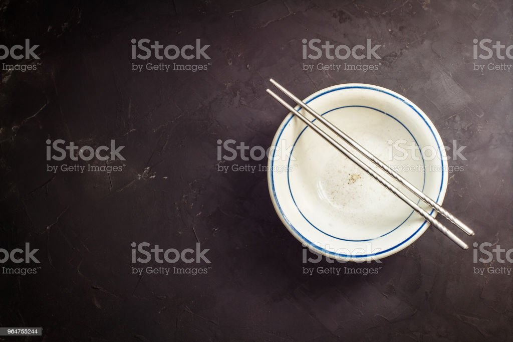 Chopsticks and cups on black table royalty-free stock photo