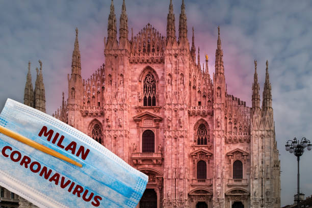 Chopsticks holding a blooded protective face mask before Duomo Milano Cathedral, to illustrate Wuhan 2019-nCoV virus worldwide spread. stock photo